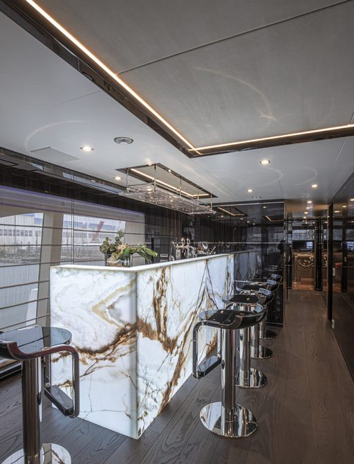 backlit onyx bar on luxury yacht 'happy me' with barstools and cinema screen