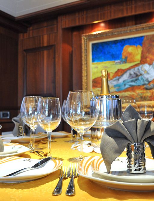 Dining table set-up on board superyacht  CONQUISTADOR, with oil paining and wine glasses