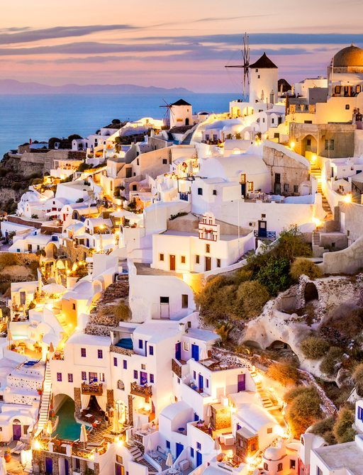 santorini at sunset, with town of oia and blue and white buildings