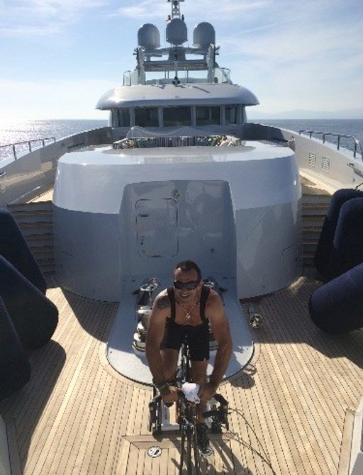 bike rider from cogs for cancer ancona to antibes training by cycling on deck of luxury superyacht