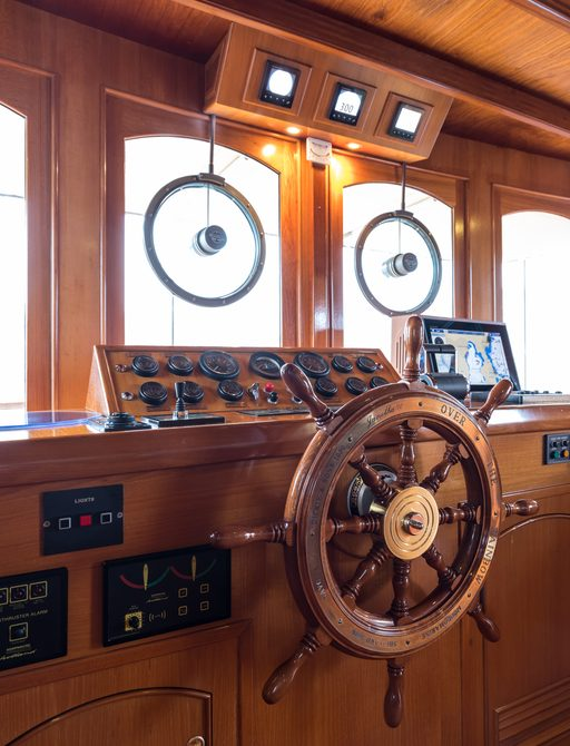 detailed shot of wheel on classic motor yacht over the rainbow with control panels in background