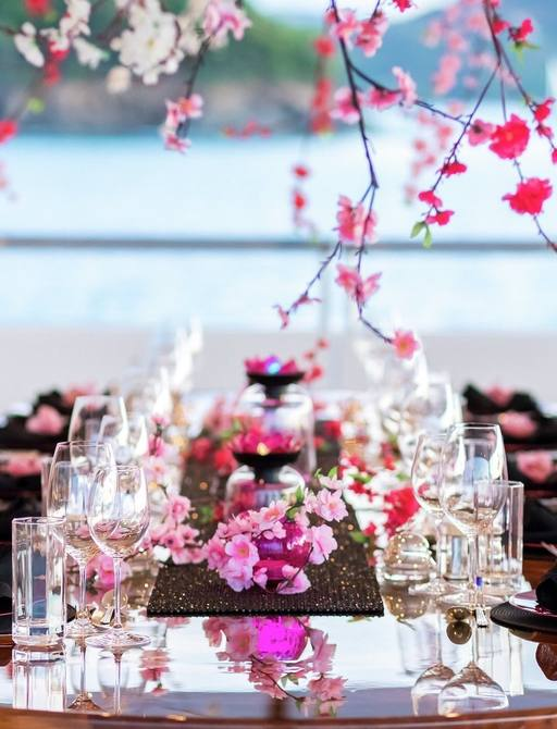 detailed shot of cherry blossom decoration on al fresco dining set up on luxury yacht titania, with view of ocean in background