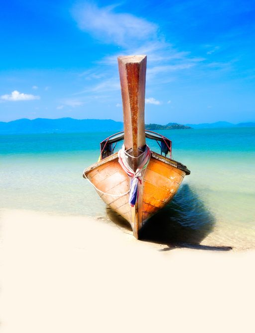 Long-tail boat on white sand beach in Thailand