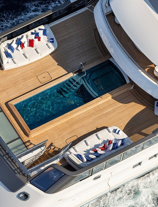 the large 12 metre swimming pool with two luxurious loungers at either side on the aft deck of lurssen's superyacht MADSUMMER