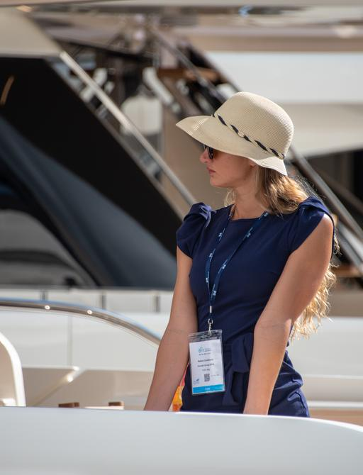 woman in designer hat on board a luxury motor yacht looking out over the marina at the impressive flewet of superyachts in FLIBS 2019
