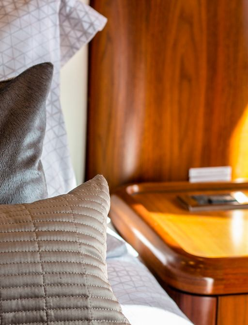 details on superyacht chess, with grey pillows and wood side table