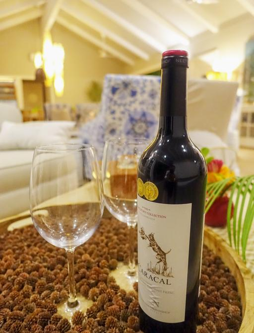detailed shot of bottle of wine and glasses in family room of villa on thanda private island