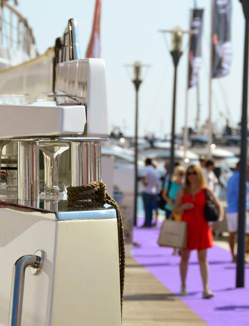 Woman walks down the boardwalk alongside yachts at Cannes Yachting Festival