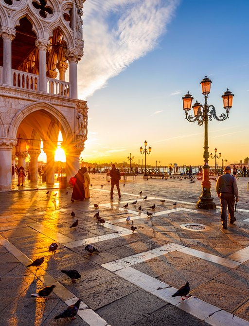 Sun sets behind doges palace in Venice.  Street lamp is centre with the view across the canals behind