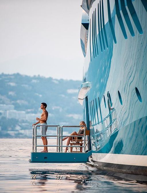 A couple enjoy their morning coffee as they overlook the Mediterranean from the comfort of charter yacht sunrays
