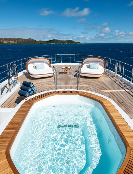 Aerial view of spa pool on superyacht DRIFTWOOD with oyster sun pads on sun deck beyond