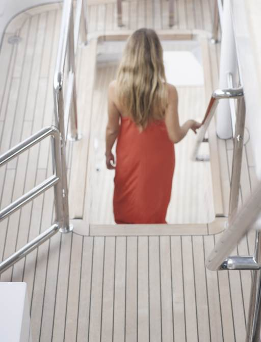 charter guest descends the staircase on the decks of superyacht RELENTLESS