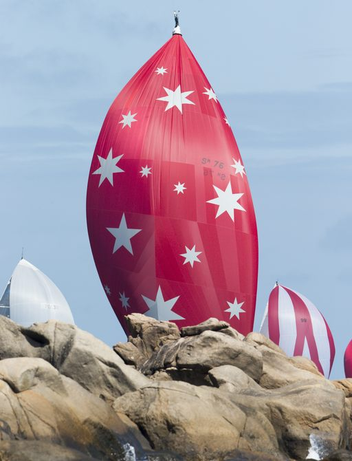 red sails visible beyond rocks participating in the Audi Hamilton Island Race Week