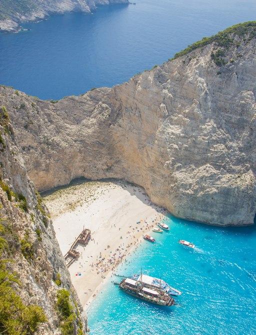 a fleet of lucury superyachts on their summer 2020 charter season in the mediteraean visit a greek beach off of the coast of myukons