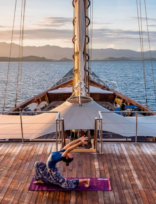 Woman does yoga on deck of LAMIMA yacht