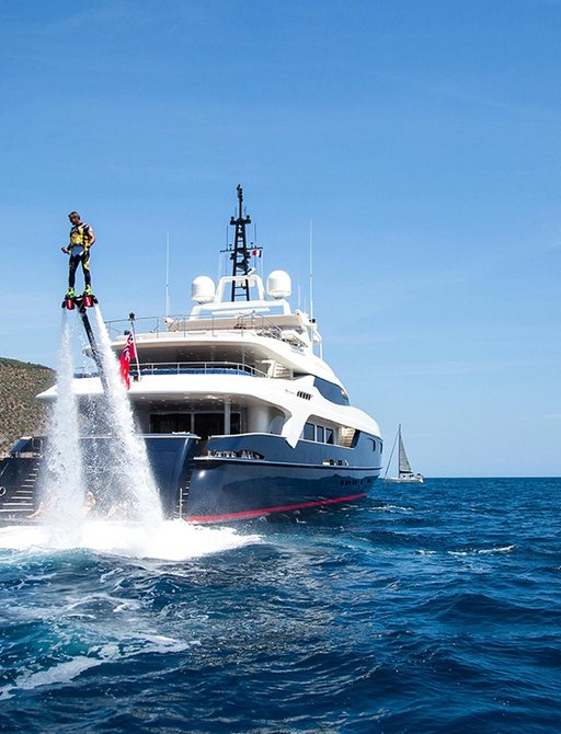 charter guest on flyboard in front of stern of motor yacht MISCHIEF