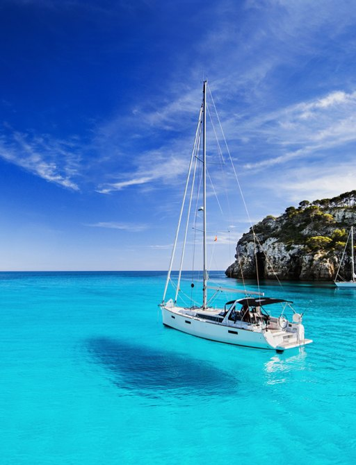 little sailing boat sits on crystal clear blue sea in mallorca