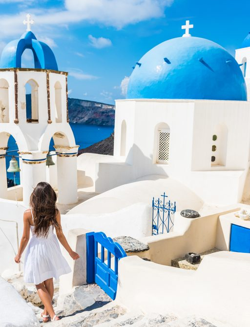 charter guest walks up stone steps on greek island of santorini