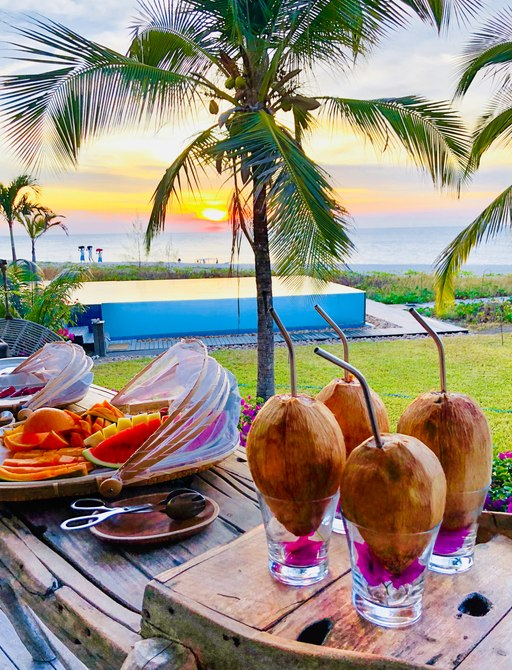 fresh coconut and spread of fruit on table on thanda island, with sun setting in background over the infinity pool