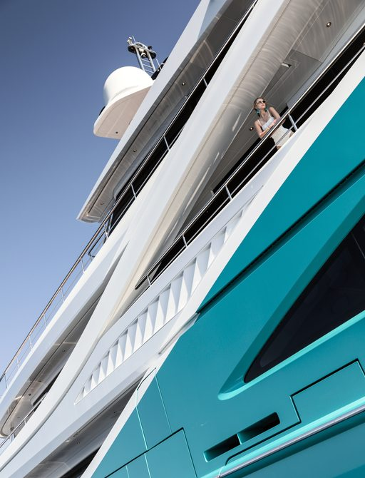 sinuous exterior lines of luxury yacht GO with turquoise-coloured hull and guest standing on side deck