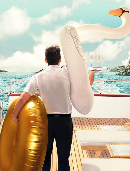 Back of crew member on boat holding inflatables and tray of drinks
