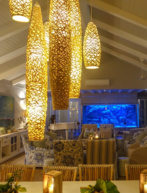 family room on thanda island, with hanging lights over dining table, sofa seating and aquarium