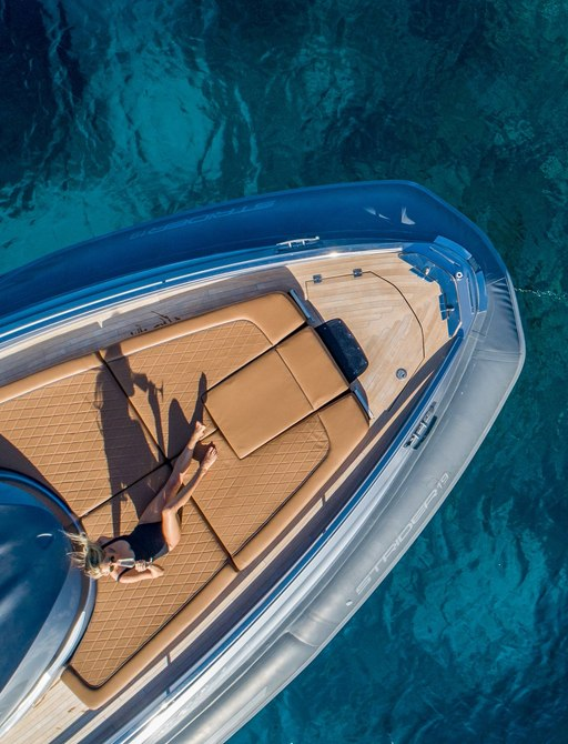woman lies on sun pads on foredeck of motor yacht driftwood aerial shot