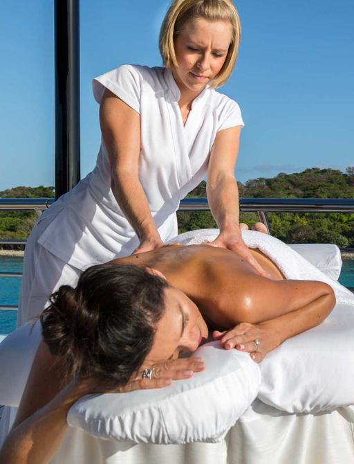 Crew on board charter superyacht gives massage to her guest on deck
