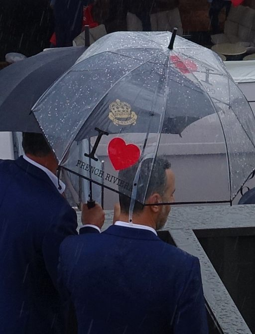 Attendees of Cannes Yachting Festival under umbrellas in the rain