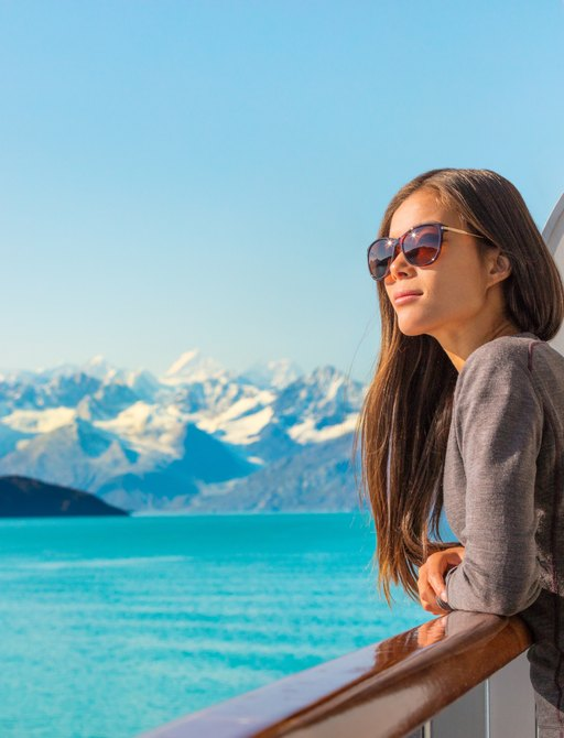 woman looks out from side of yacht at alaskan coastline, with snowy mountains and bright blue sea