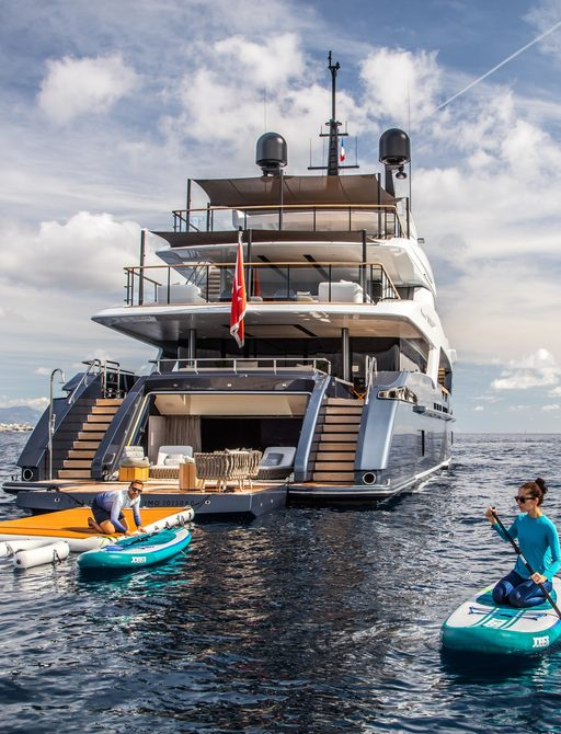 View of superyacht SEVERIN'S stern, with beach club and guest on kayak in water