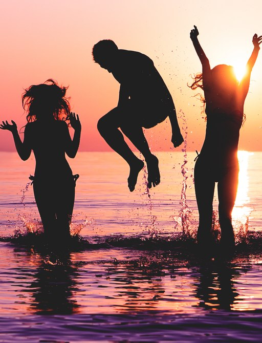 Friends celebrate in the water at sunset in Ibiza