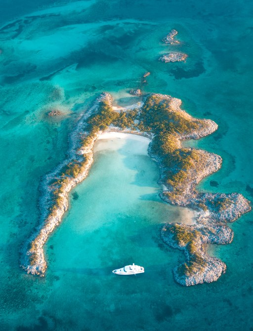 Small U shaped coral island in Bahamas viewed from above with yacht in water