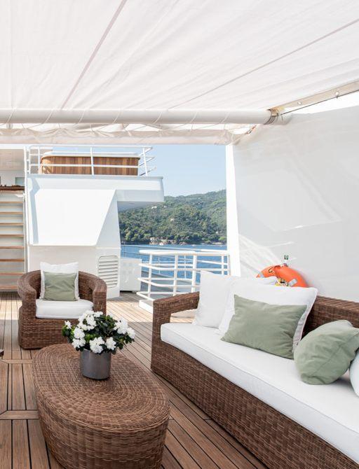 Rattan style cream furniture under shade on superyacht 'Bleu De Nimes'