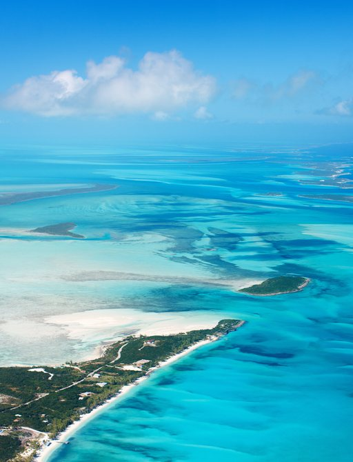 aerial view of sandbars and bright blue sea in the bahamas, with islands covered in greenery between the sand