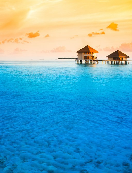 Beautiful clear water with two water bungalows on the horizon and amazing sky behind