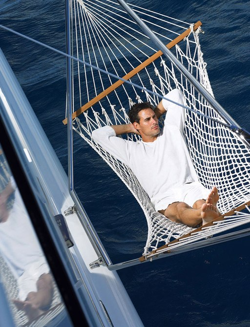 Man relaxes in hammock hanging on luxury yacht HARLE