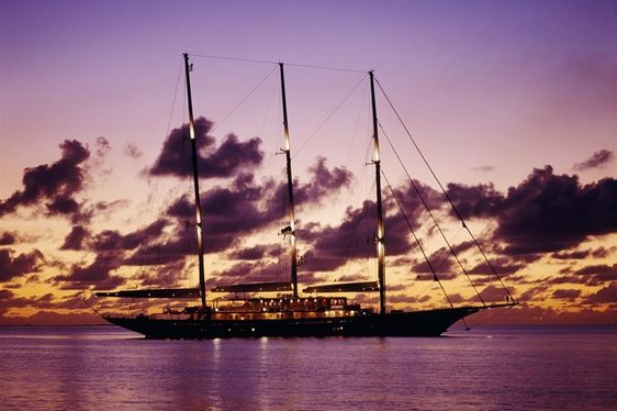Beautiful purple sun set behind sailing yacht Athena cruising on charter