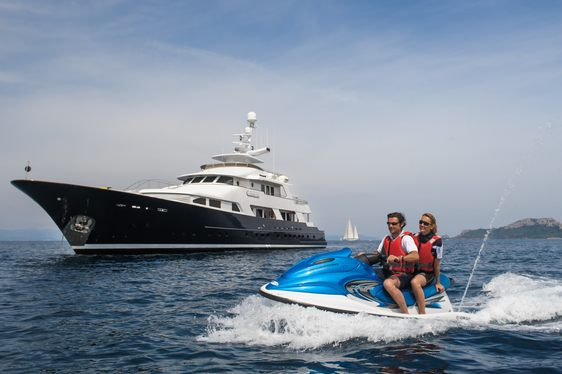 superyacht L'Albatros cruising on charter alongside charter guests on a jet ski