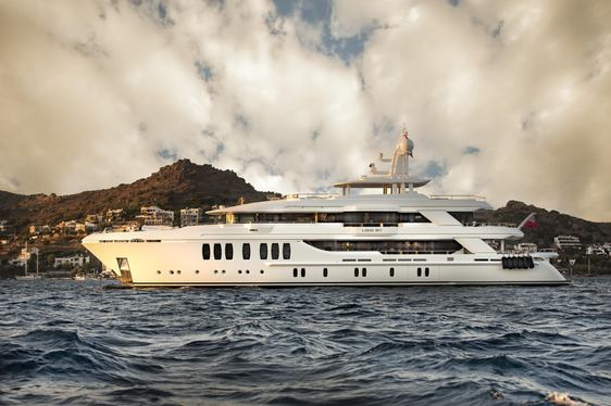 The port side profile of a white superyacht in front of a mountain