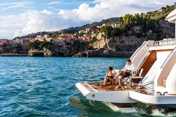 charter guests relax on the drop-down swim platform of luxury yacht December Six