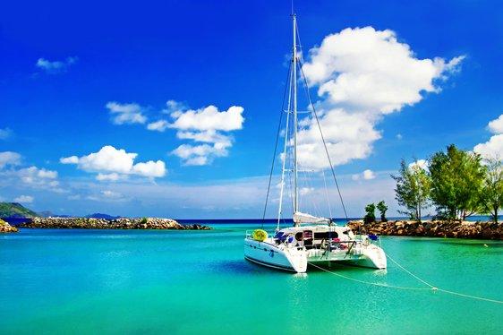 A catamaran anchored by a deserted beach in the Seychelles