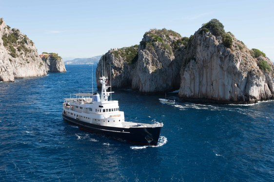 Luxury yacht Ice Lady sailing past large rock on charter in Mediterranean