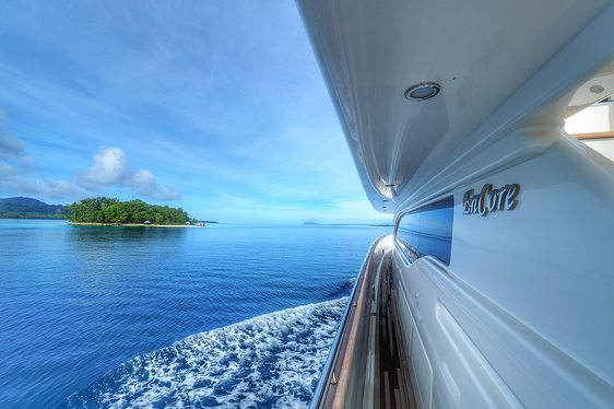 side deck of motor yacht ENCORE with a tiny South Pacific island in the distance