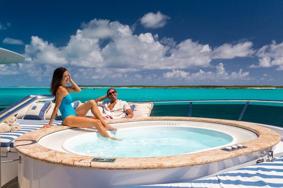 charter guests relax by the Jacuzzi on the sundeck of superyacht Lady Joy