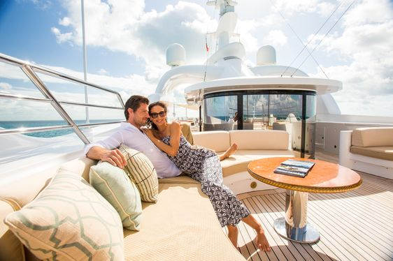 charter guests sit together in the seating area on the sundeck of motor yacht Lumiere II