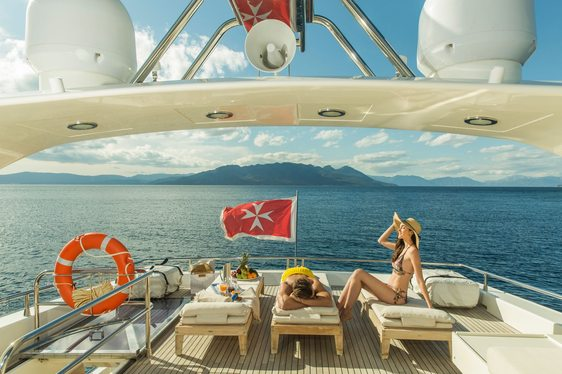 charter guests relax on the loungers on the sundeck of luxury yacht THEORIS