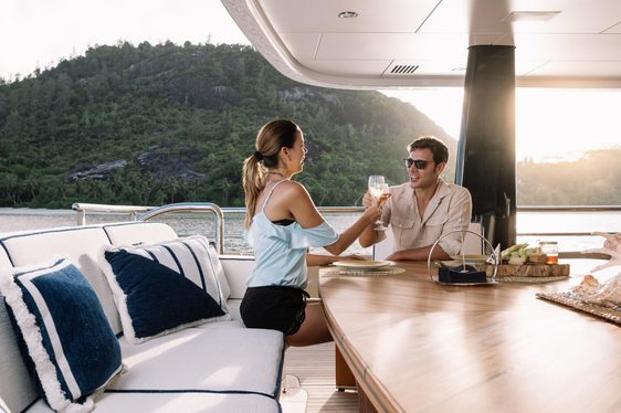 guests enjoy a drink together on the private master suite deck area aboard superyacht LILI