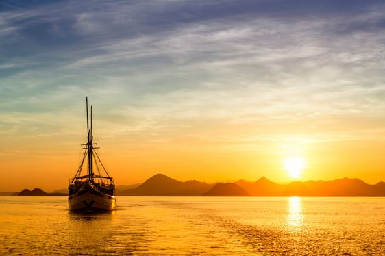 a luxury gulet anchors in the waters off Komodo Island in Indonesia as the sun sets