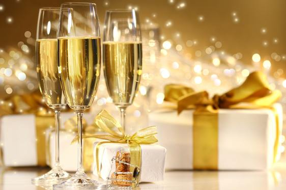 Three champagne flutes on a table covered with presents